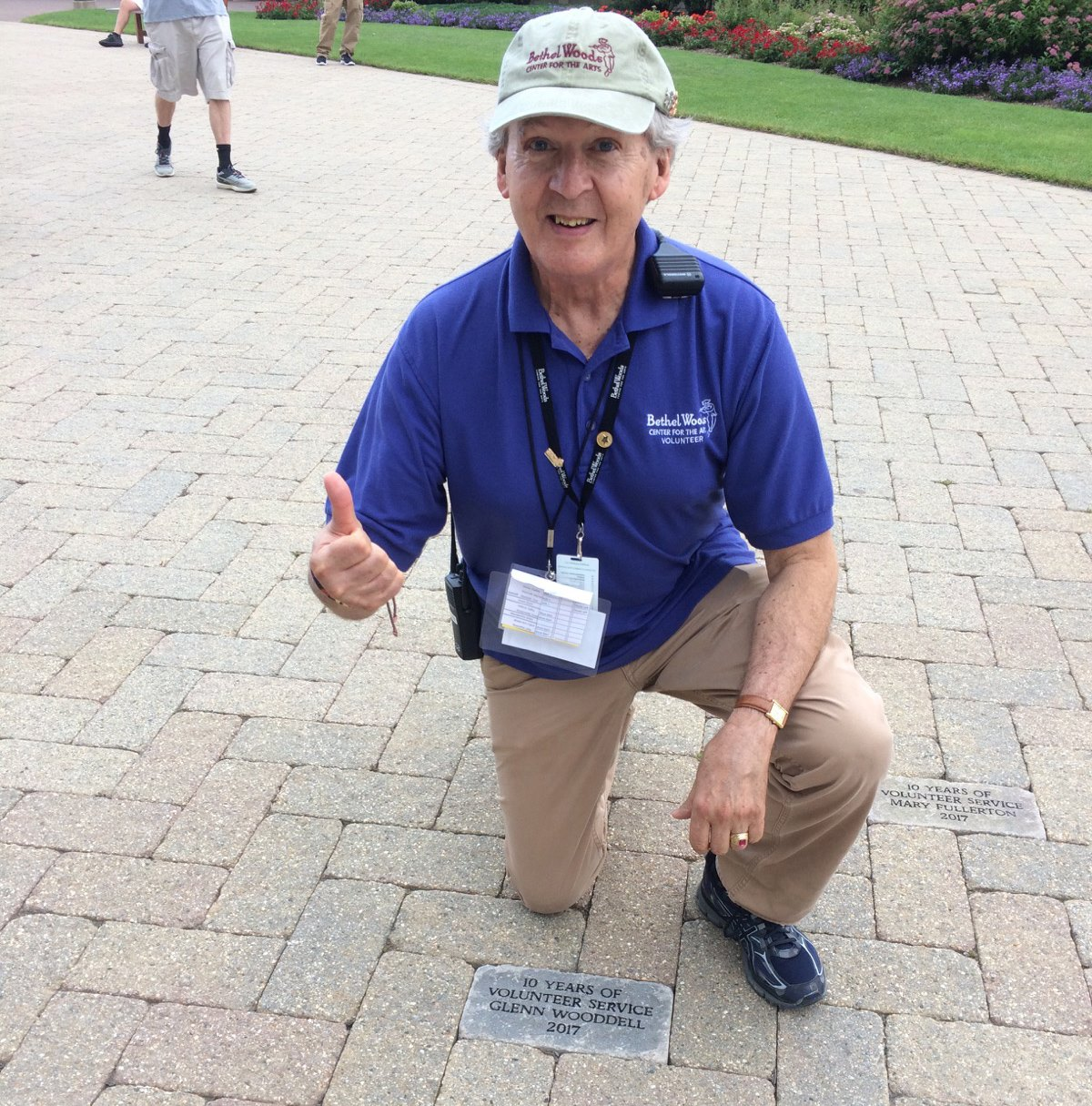 volunteer glenn woodell kneeing by commemorative paver