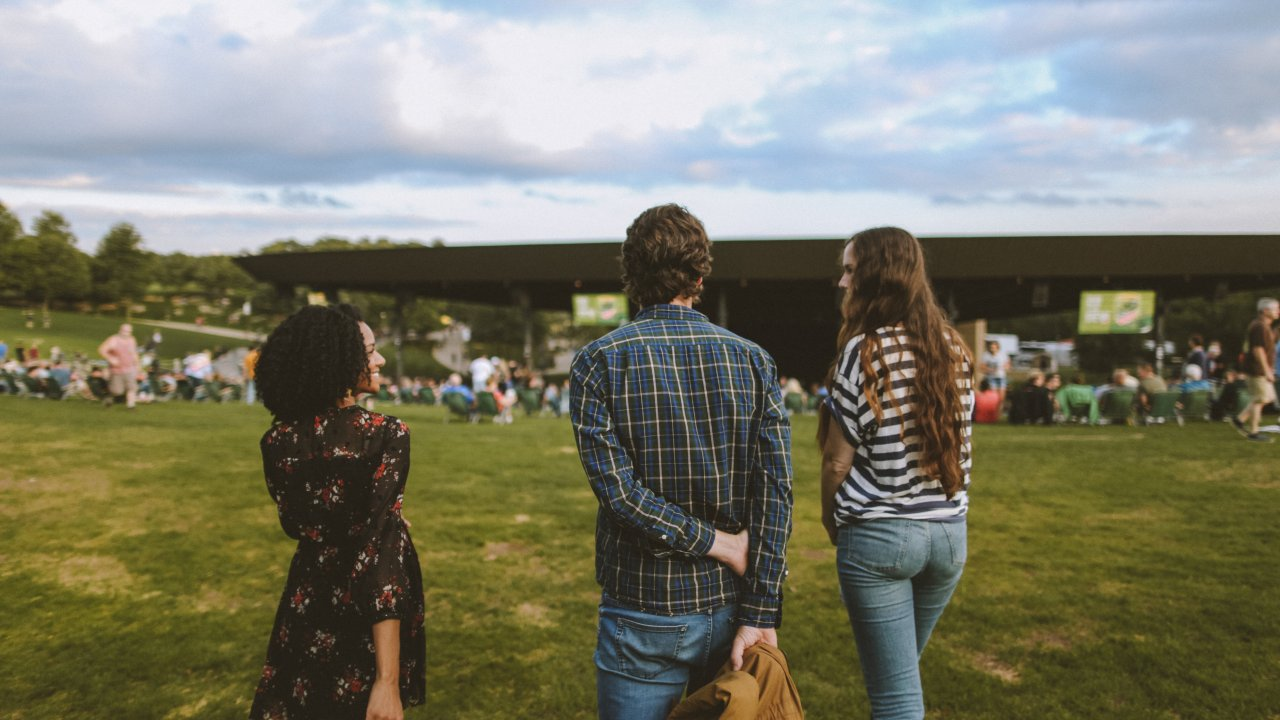shot behind of three people at outdoor concert