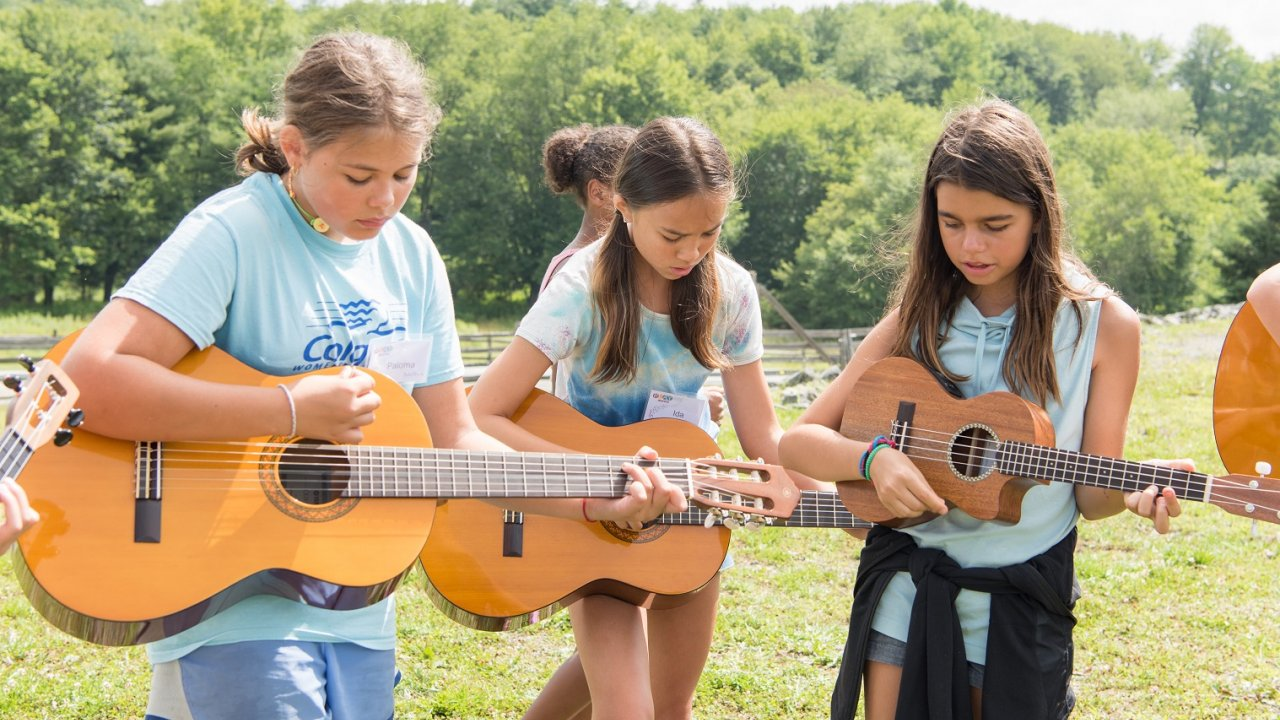 three girls playing guitars during a Bethel Woods music program