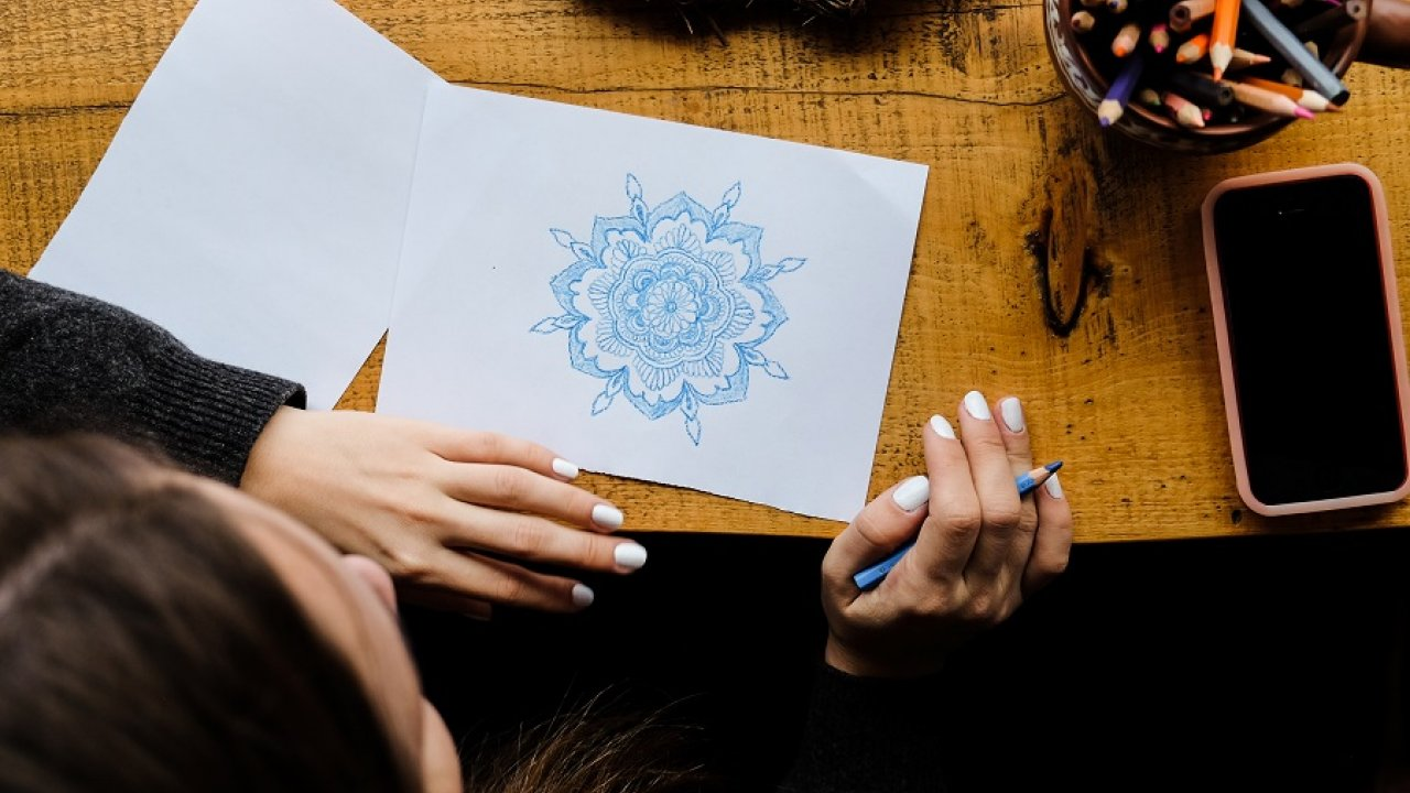 woman making mandala art