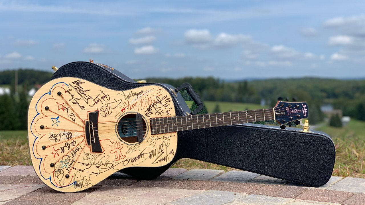 guitar signed by multiple musicians with case available at the auction