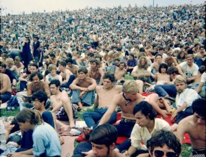 Crowd at Woodstock sitting in a crowded farm field
