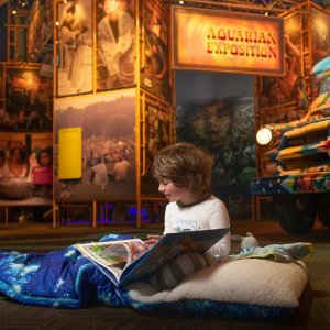 little boy reading a book while sleeping over at the Bethel Museum
