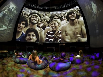 people sitting on bean bag chairs watching video of Woodstock at the Museum at Bethel Woods