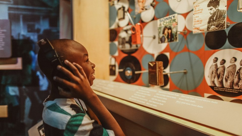 boy listening to an interactive exhibit at Bethel Woods Museum