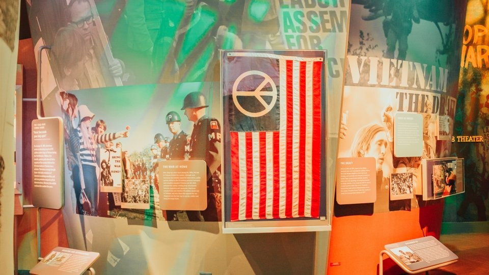 Museum exhibit at Bethel Woods about Vietnam with interpretive panels and an American flag with a peace sign where the stars would be